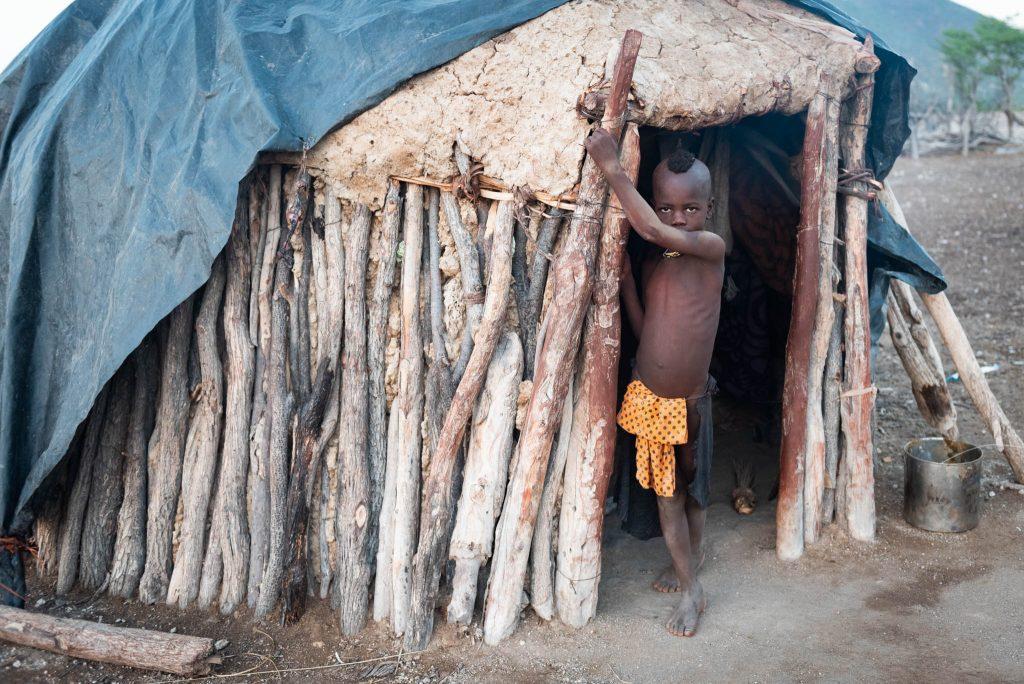 Bambino Himba con Casa Tipica di Sterco e Legno