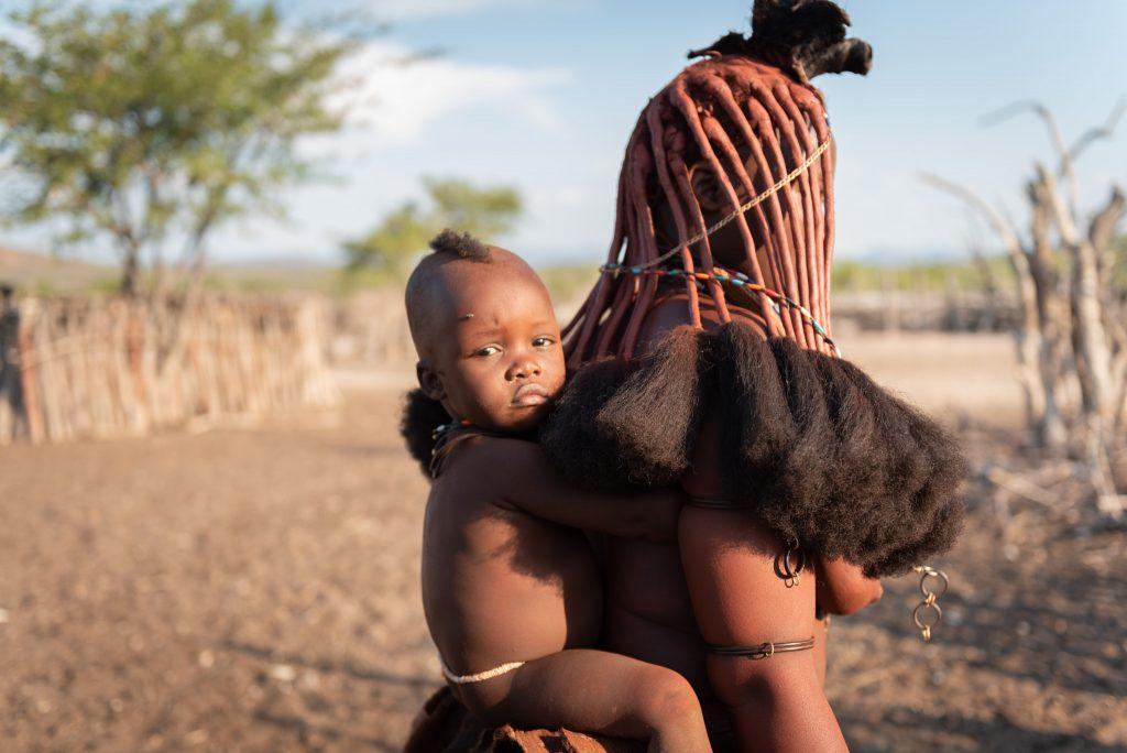 Bambino Himba sulle spalle di una donna Himba